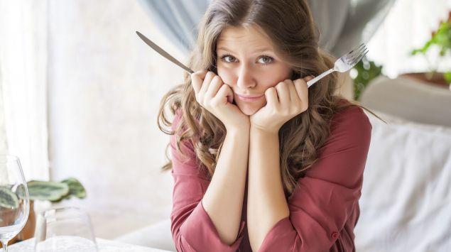 Das Bild zeigt eine Frau am Tisch sitzend mit Messer und Gabel in der Hand.