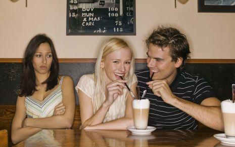 Das Bild zeigt einen Mann und eine Frau, die zusammen aus einem Glas trinken und eine eifersüchtige Dritte.