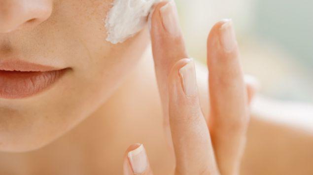 Eine Frau cremt sich im Gesicht ein.