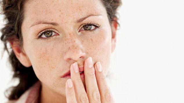 Das Bild zeigt eine Frau mit Sommersprossen, die sich mit einer Hand an die Lippen/ den Mundwinkel fasst.