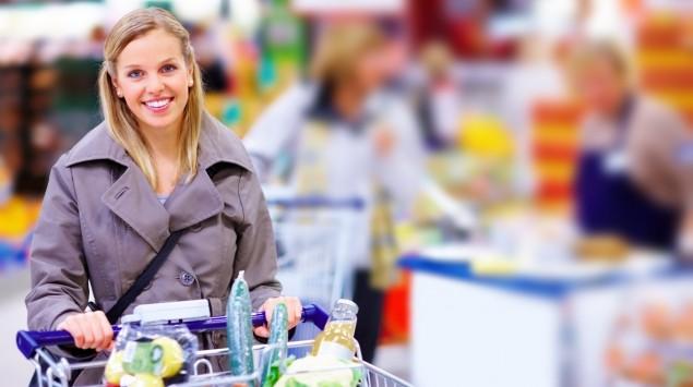Eine Frau schiebt einen Einkaufswagen mit Obst und Gemüse durch den Supermarkt.