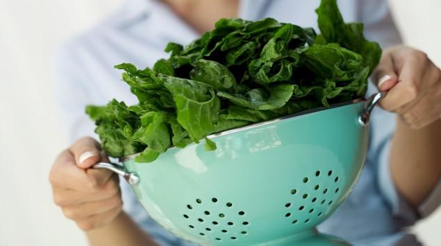 Das Bild zeigt eine Frau mit einem Sieb voll Spinat.