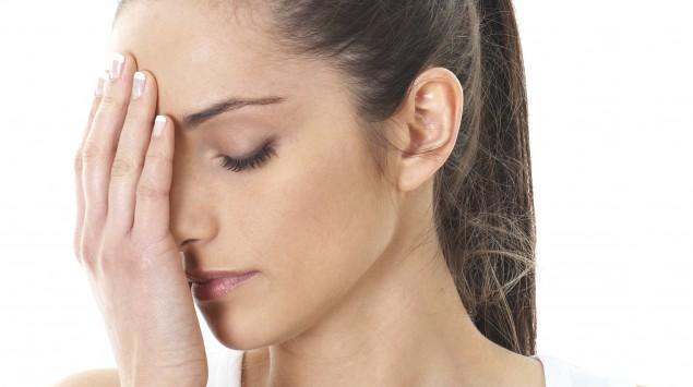 Das Bild zeigt eine Frau, die sich ans Auge fasst und Tabletten in der Hand hält.