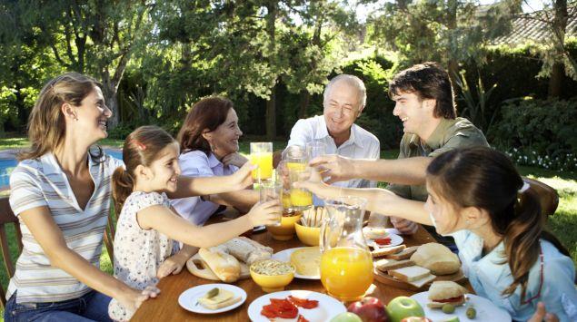 Das Bild zeigt eine Familie draußen beim Essen.