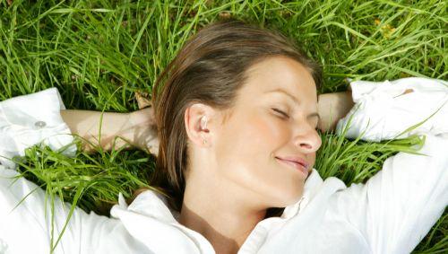 Das Bild zeigt eine Frau, die im Gras liegt.