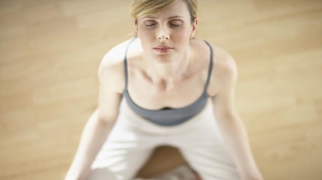 Das Bild zeigt eine Frau im Schneidersitz meditierend.
