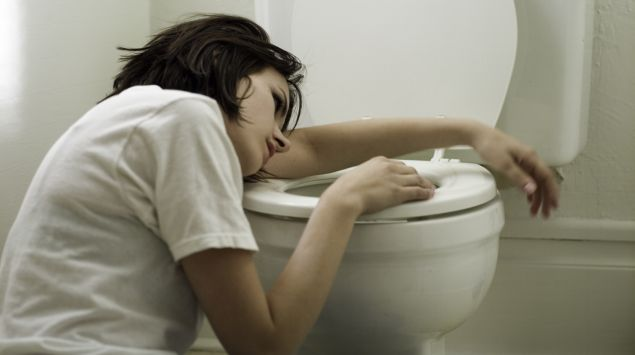 Das Bild zeigt eine Frau, die am Rand einer geöffneten Toilette gestützt liegt.