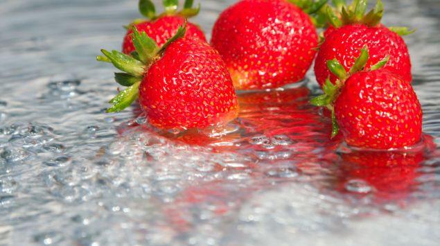 Erdbeeren liegen in einer Pfütze aus Wasser.