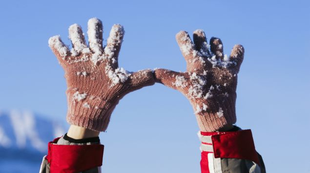 Das Bild zeigt eine Person mit Handschuhen im Schnee.