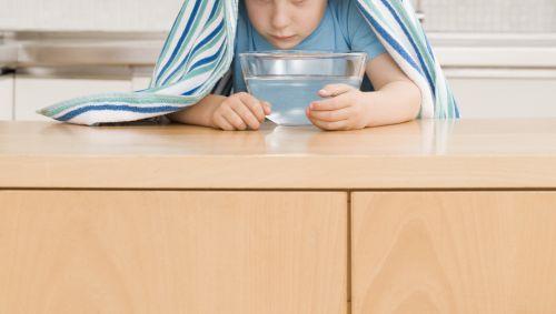 Das Bild zeigt einen Jungen beim inhallieren.