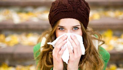 Eine Frau in herbstlicher Umgebung putzt sich die Nase.