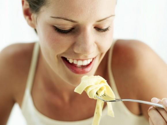 Gastritis: Das Bild zeigt eine Frau, die Nudeln isst.