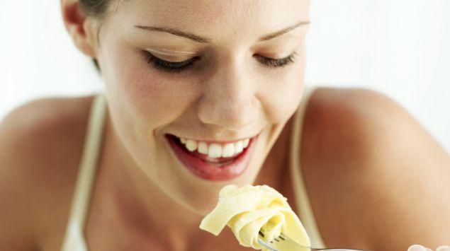 Das Bild zeigt eine Frau, die Nudeln isst.