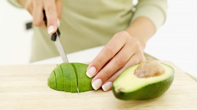 Das Bild zeigt eine Frau, die eine Avocado aufschneidet.