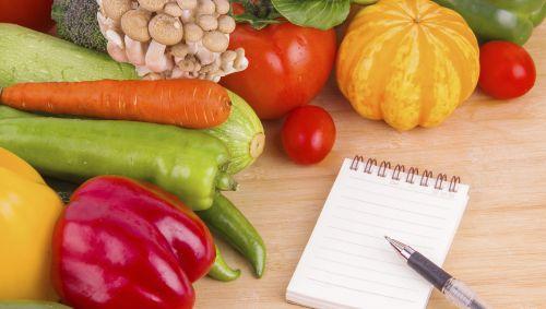 Verschiedenes Gemüse, daneben ein Notizblock.