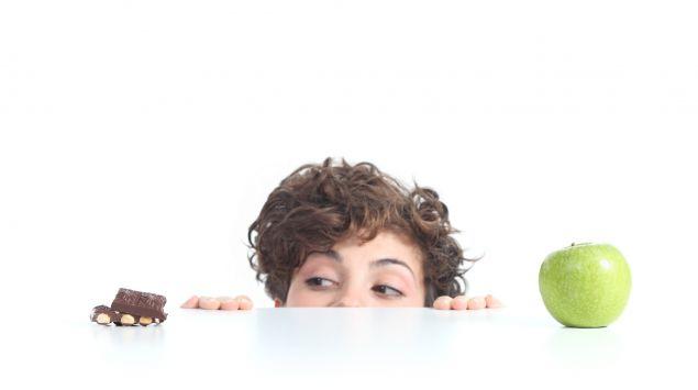 Eine Frau hat einen Apfel und eine Tafel Schokolade zur Auswahl.