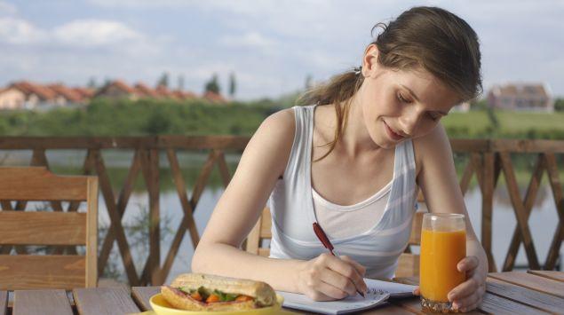 Das Bild zeigt eine Frau schreibend an einem Tisch mit ihrem Mittagessen vor ihr.