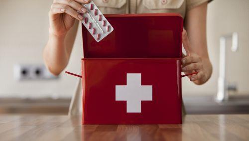 Das Bild zeigt eine Frau, die eine Packung Tabletten in einen Erste-Hilfe-Koffer packt.