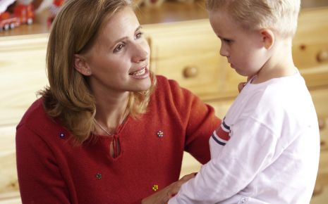Eine Mutter spricht mit ihrem traurig aussehenden Jungen.
