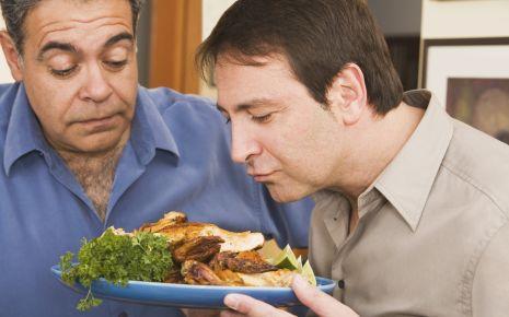 Ein Mann riecht an einem Teller mit Essen, ein anderer steht daneben.