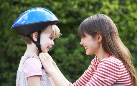 Eine junge Mutter setzt ihrem Sohn einen Fahrradhelm auf.
