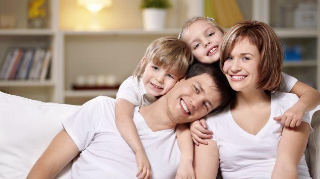 Man sieht eine junge Familie auf einem Sofa.