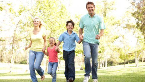 Eine fröhliche Familie läuft über eine Wiese.