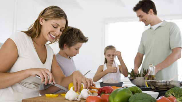 Man sieht eine Familie, die Gemüse schneidet.