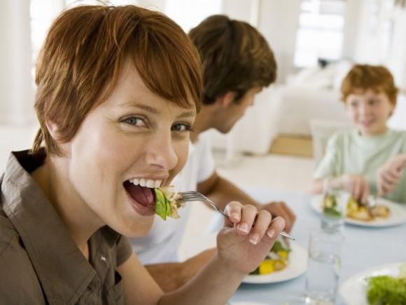 Eine Frau führt eine Gabel mit Essen zum Mund. Im Hintergrund sieht man einen Mann und einen Jungen mit am Tisch sitzen.