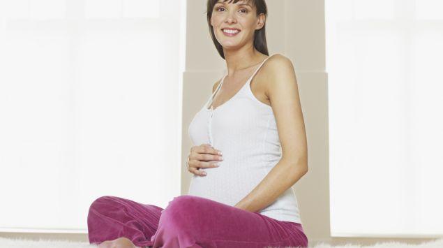 Das Bild zeigt eine sitzende Schwangere.