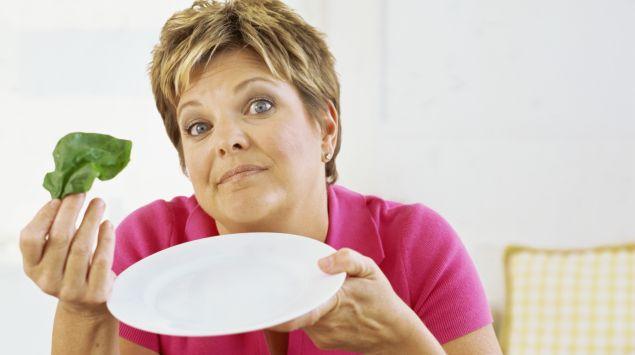 Das Bild zeigt eine Frau mit leerem Teller und einem Salatblatt in der Hand.
