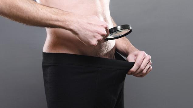 Ein Mann schaut mit einer Lupe auf sein Geschlechtsteil.