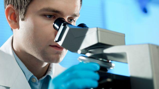 Man sieht einen Mann, der durch ein Mikroskop blickt.