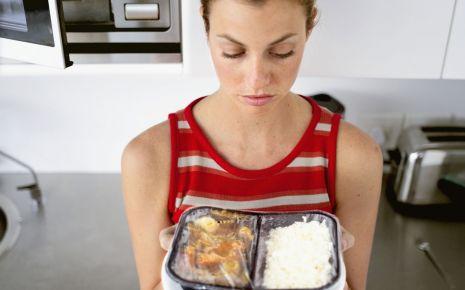 Eine Frau betrachtet einen Teller mit einem Mikrowellen-Menü.