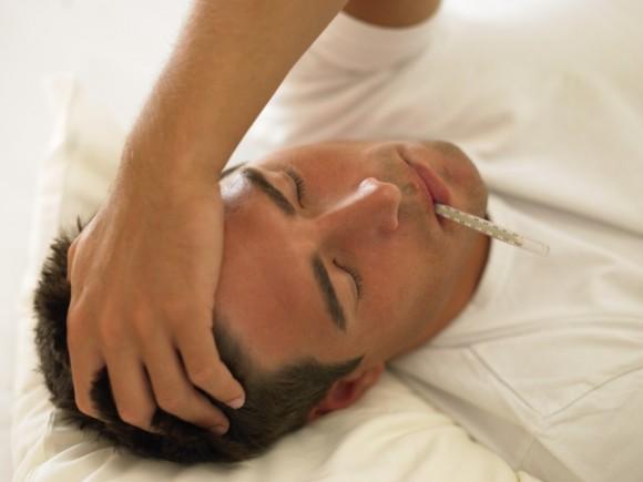Das Bild zeigt einen Mann mit Kopfschmerzen und einem Fieberthermometer im Mund.