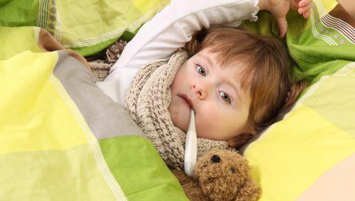 Das Bild zeigt einen Jungen, der mit Fieberthermometer im Bett liegt.