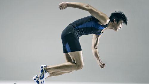 Das Bild zeigt einen asiatischen Sprinter, der aus einem Startblock startet.