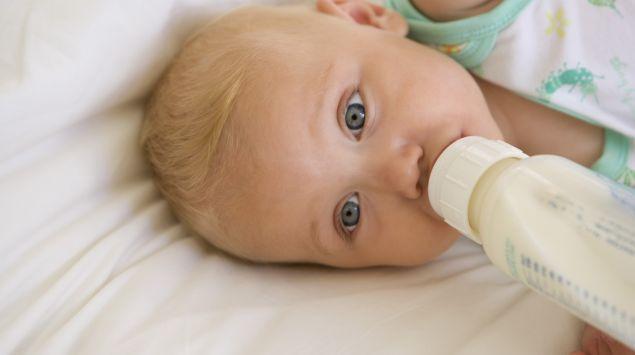 Das Bild zeigt ein Kind, das ein Fläschchen trinkt.
