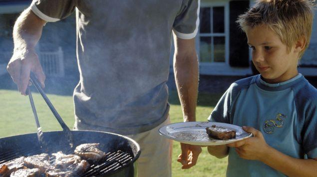 Ein Vater und sein Sohn grillen im Garten Fleisch.