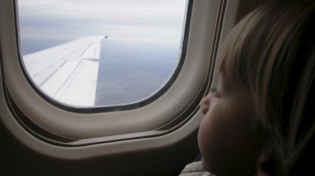 Kleiner Junge schaut aus dem Fenster eines Flugzeugs.