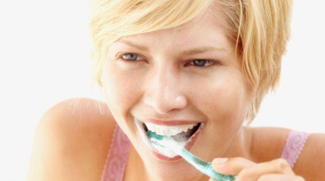 Das Bild zeigt eine Frau, die Zähne putzt.