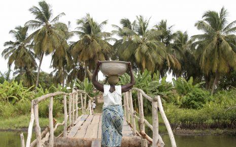 Onchozerkose: Eine afrikanische Frau trägt eine Schüssel über eine Brücke.