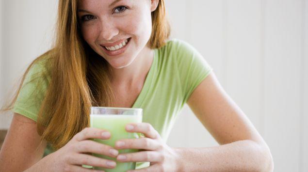 Das Bild zeigt eine Frau, mit einem Getränk in der Hand.