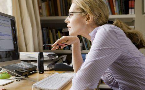 Eine Frau sitzt am Computer und betrachtet den Bildschirm.