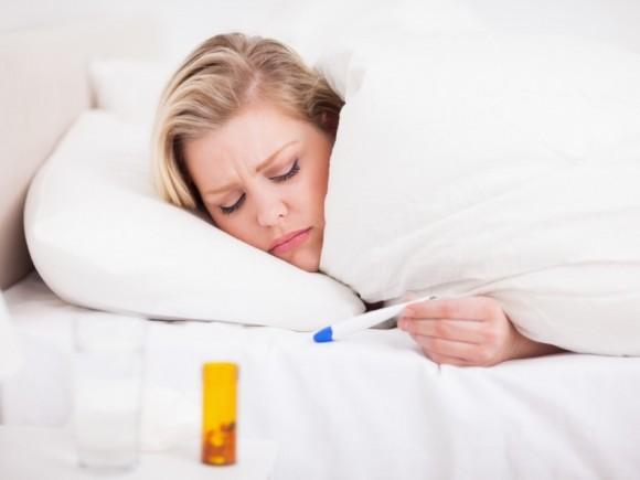 Pfeiffersches Drüsenfieber: Eine Frau liegt im Bett und liest das Fieberthermometer ab.