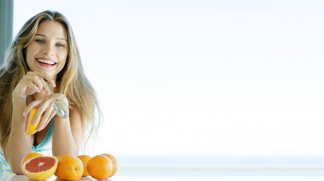 Eine junge Frau isst eine Grapefruit.