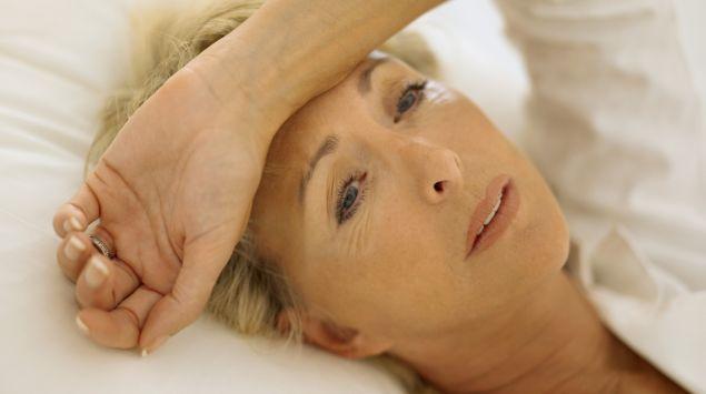 Eine Frau liegt leidend im Bett.