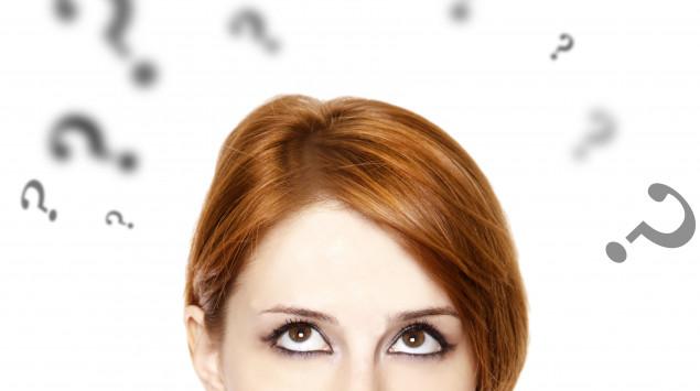 Eine junge Frau blickt fragend, um sie herum einige Fragezeichen.