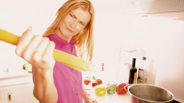 Eine Frau hält mit fragendem Blick eine handvoll Spaghetti in der Hand.