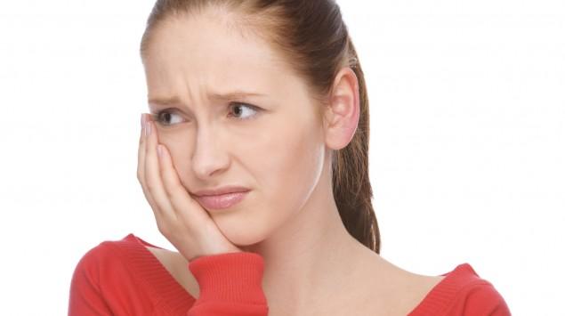 Eine Frau hält sich schmerzvoll eine Hand an die rechte Wange.